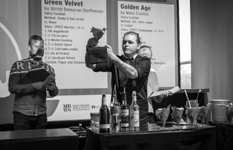 Ulrich Deleuran Steffensen præsenterer den færdige cocktail for dommerne og for folk i salen. Photo by Michael Sperling.