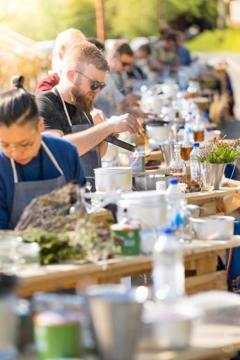 Deltagerne er klar til kreere deres cocktails ved hver deres udendørs køkken. Photo by Michael Sperling